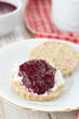 Scone with goat cheese and jam on a plate closeup vertical