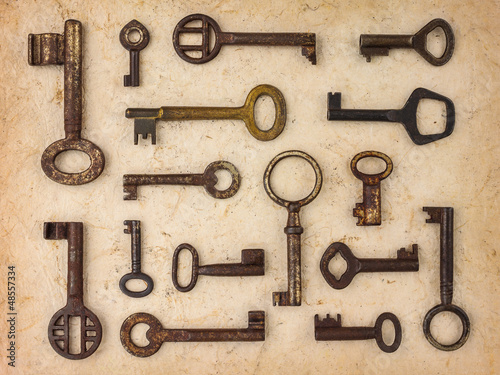 Different antique keys on a retro paper background