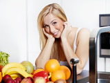Pretty girl in the kitchen eating healthy food to lose weight