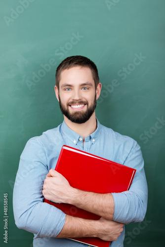 lächelnder student mit aktenordner vor der tafel