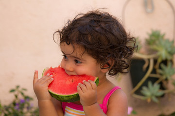 Young child eating watermelon in summer