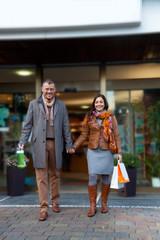 Paar mit Einkaufstüten vor einem Geschäft