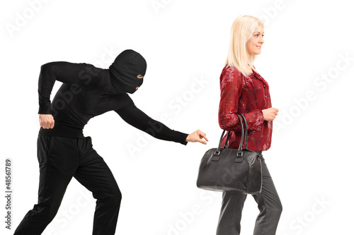 A pickpocket with mask trying to steal a from a woman carrying a