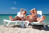 Young couple sunbathe on the beach bed on the sea beach