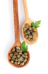 green capers in wooden spoons on white background close-up