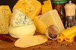 Various types of cheese on wooden table close up