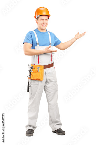 Full length portrait of a manual worker with tool belt and helme