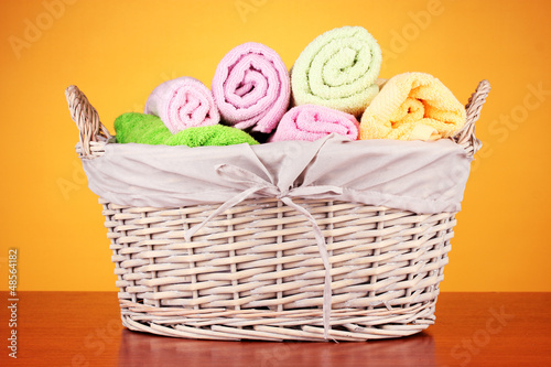 Colorful towels in basket on color background