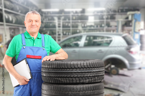 Mature mechanic posing on a tires in front of car at repair shop