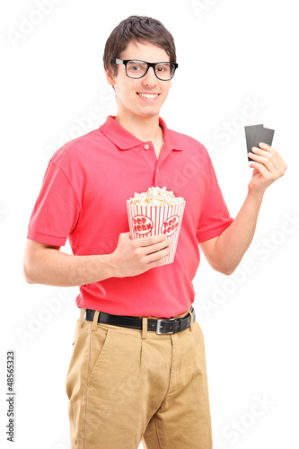 Smiling man holding a popcorn and two tickets for cinema