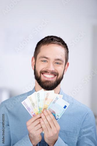 lächelnder junger mann mit geldscheinen