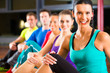 Group of people and instructor in gym stretching