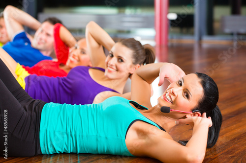Fitness group in gym doing crunches for sport