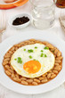fried egg with beans on the plate and glass of water