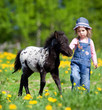 Child and foal in the field at spring.