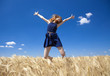 Redhead girl at wheat field in summer day. Photo with bokeh at b