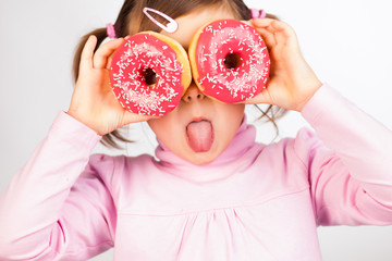Girl looks through donuts