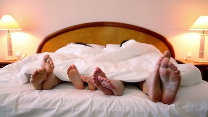 Family lay in bed and move bootless feet