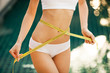 Woman measuring her waistline. Perfect Slim Body. Outdoor