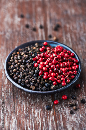 Black and pink peppercorns on a small plate