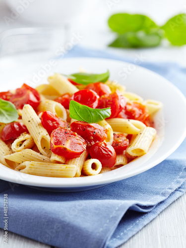 Penne pasta with cherry tomatoes and basil leaves