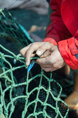 Fisher darning fish seine with net needle