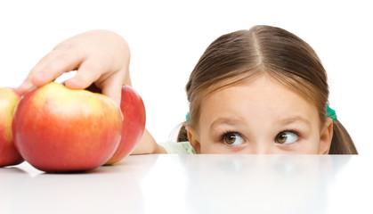 Little girl is reaching apple