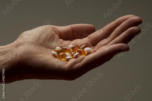 Closeup of  hand holding vitamin E and vitamin D capsules