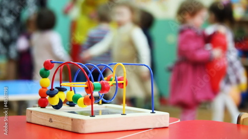 conundrum toy standing on table, in defocus children play
