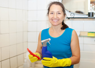 woman cleans bathroom with rug and cleaner