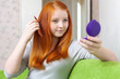 red-haired girl combing  hair