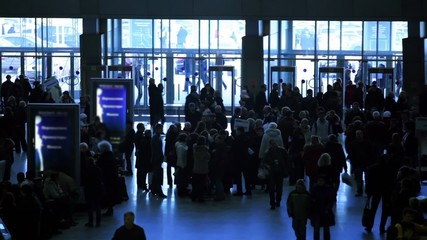 people walk around near entrance with glass walls at station