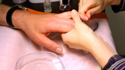 In course of manicure cosmetician rubs butter in of man fingers