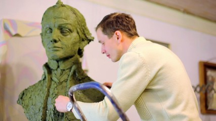 Sculptor puts pieces of clay on unfinished A.Suvorov bust