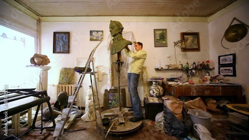 Sculptor work with clay below his composition on wooden support