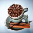 Coffee beans, vanilla and cinnamon in a blue cups