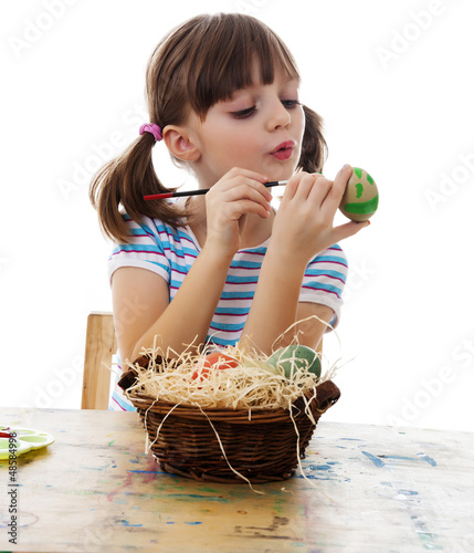 little girl coloring easter eggs white background