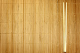 Fototapety Bamboo mat and chopsticks food background