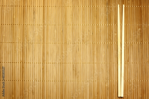 Bamboo mat and chopsticks food background