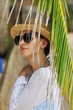 Woman in sunglasses near palm tree