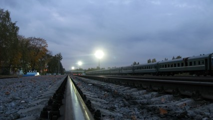 Passenger train stands at railway station before empty rails