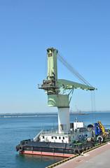 Floating cargo crane over blue sky background
