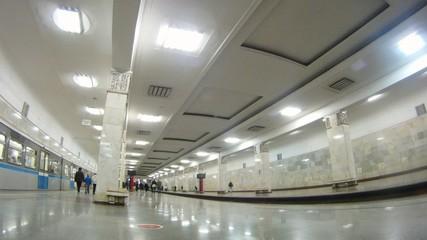 Passengers go on ladder on subway station where three railway