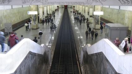 People wait trains on subway station where three railway ways