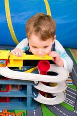 Kleiner Junge spielt mit Parkhaus für Autos