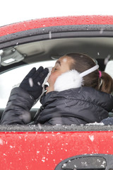 Cute girl with flu symptoms sneezes in a car on snowy day