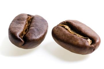 zwei Espressobohnen vor weißem Hintergrund