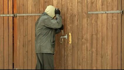 Robber trying to break the garage door