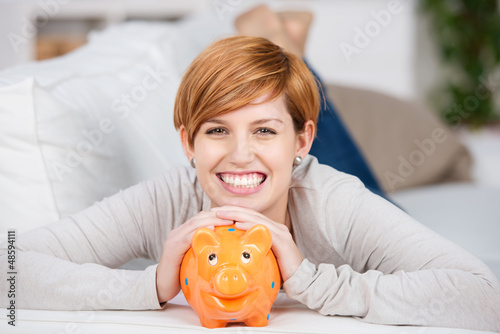 lachende junge frau mit sparschwein