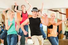 Zumba lub Jazzdance - młodzi ludzie tańczą w studiu